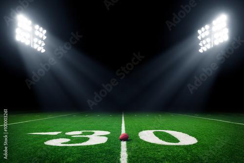 Football field illuminated by stadium lights Poster