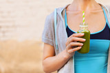 Woman drinking vegetable smoothie after fitness running workout
