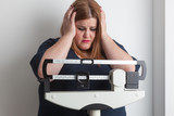 worried woman on a medical weight scale