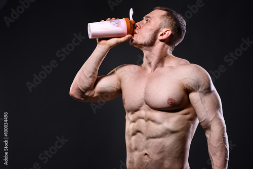 fototapeta na ścianę Athlete man drinking protein over dark background