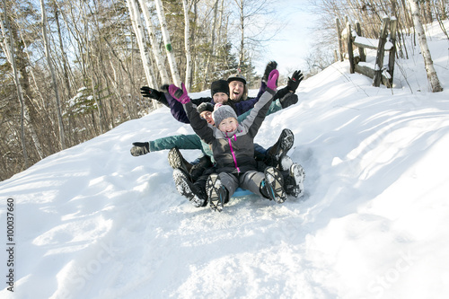 kids with parents is sledging in winter-landscape