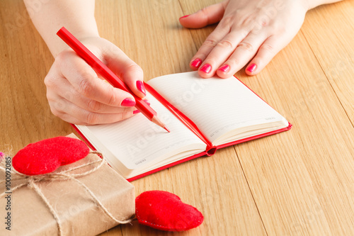 Woman hands drawing or writing, gift box, red hearts on wooden t © Andrey Cherkasov