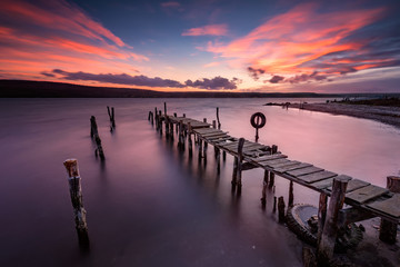Lake sunset. Magnificent long exposure lake sunset with an old wooden pier. © jessivanova