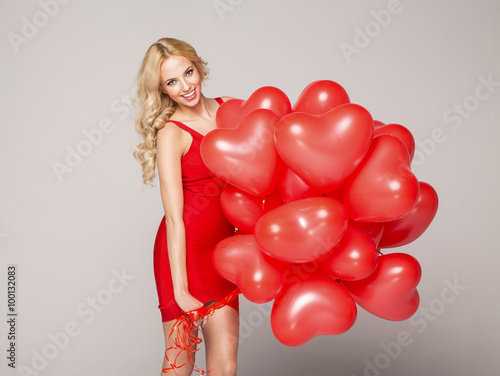 Poster Beautiful blond woman posing on grey background in red dress, ho