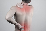 Man with neck and back pain. Man rubbing his painful back close up. Pain relief concept