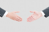 ビジネスマン同士の握手,灰色背景