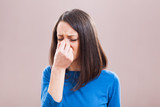 Portrait of young woman who is having pain in her sinus.