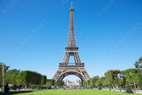 Eiffel tower, sunny summer day with blue sky and green Field of Mars Photo by andersphoto