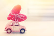 Miniature car carrying red heart cushion