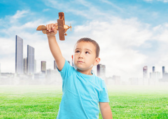 portrait of a little boy playing with a wooden plane