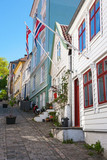 Fototapety Street with old wooden houses and Norwegian flags in Bergen