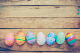 Fototapety Easter eggs on wooden background with vintage tone.