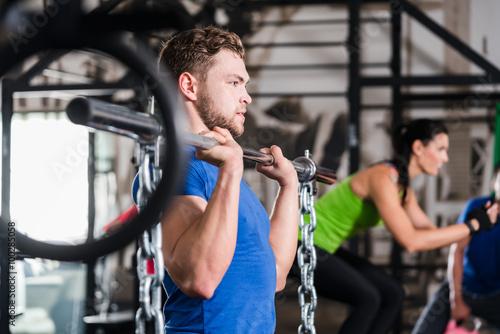 mata magnetyczna Mann im Fitnessstudio bei Functional Fitness Sport mit Hantel und Kette