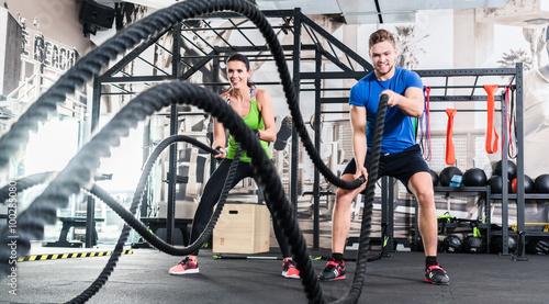 mata magnetyczna Frau und Mann im Fitnessstudio mit battle rope