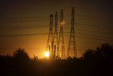 Electricity pylon towers glowing in late glow of sun setting