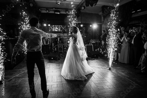 Beautiful newlywed couple first dance at wedding reception surrounded by smoke and lights and sparks b&w