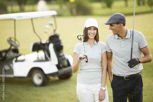 Fototapeta Young couple at golf cart