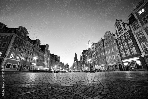 Fototapeta Cobblestone historic old town in rain at night. Wroclaw, Poland. Black and white