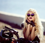 Biker girl in helmet sitting on vintage custom motorcycle.