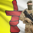 Soldier with machine gun and Canadian province flag on background series - Nunavut