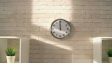 Zoom in of circle clock on brick office wall showing midday