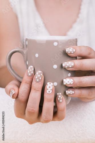 Beauty treatment photo of nice manicured woman fingernails holding a cup. © tamara83