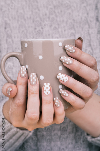 Manicure - Beauty treatment photo of nice manicured woman fingernails holding cup. © tamara83