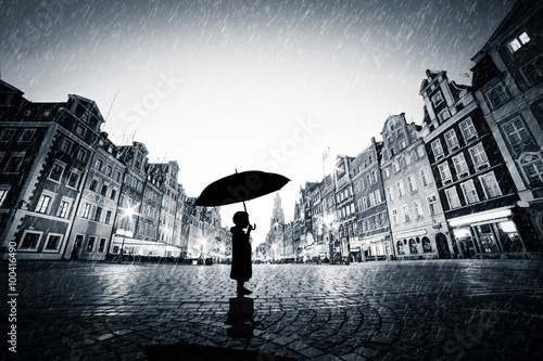 Child with umbrella standing alone on cobblestone old town in rain