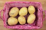 gruppo di sei patate in un cestino rosa con vista dall