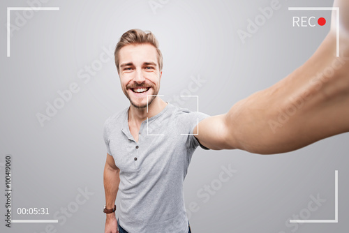 canvas print picture Handsome man takes a video of himself