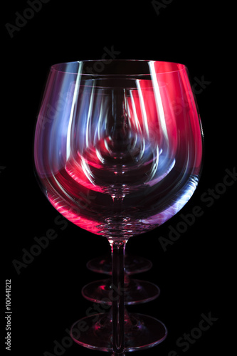 Fototapeta Party wine glasses in nightclub lit by red, blue, lilac lights, nightlife and entertainment industry, objects in row isolated on black background