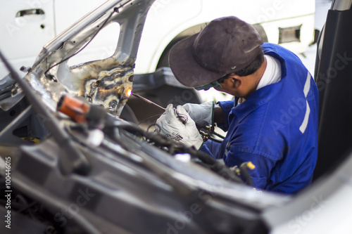 Man mechanical worker repairing a car body in a garage Poster