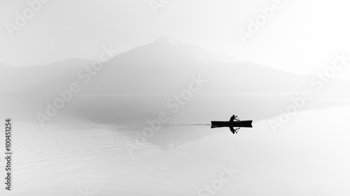 mata magnetyczna Fog over the lake. Silhouette of mountains in the background. The man floats in a boat with a paddle. Black and white