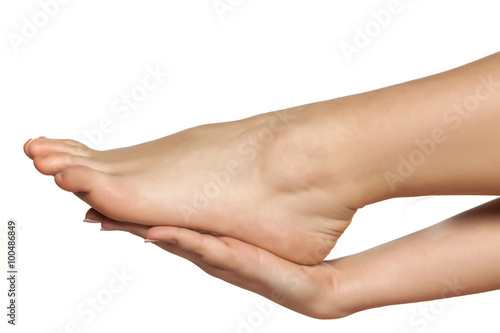 female hand holds the bare female foot