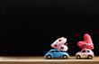 Obrazy na płótnie, fototapety, zdjęcia, fotoobrazy drukowane : Miniature pink and blue cars carrying hearts