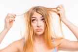 Fototapety Sad girl looking at her damaged hair