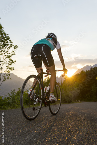 Poster cyclist from behind with sunset