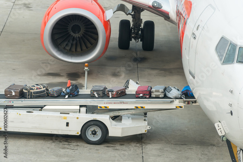 Poster Luggage loading into a plane in an airport