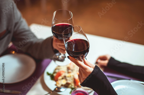 Beautiful young couple with glasses of red wine in luxury restaurant - 100632486