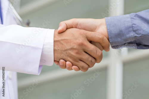 Doctor shakes hands with a patient плакат