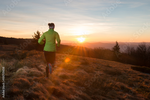 Fotografiet woman from back running on the trail in the mountains with first ray of light in