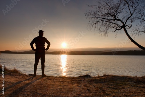 Papiers peints Morning Glory Tall hiker in dark sportswear with poles and sporty backpack on beach enjoy sunset at horizon with blue sky with clouds.