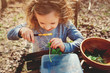 child girl exploring nature in early spring, looking at first sprouts with loupe. Teaching kids to love nature.
