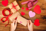 Hearts, gift, ribbons, envepopes on wood background. Woman