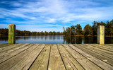 Fototapety Summer Day At The Lake. Wooden dock overlooking a gorgeous lake in the wilderness. Ludington State Park. Ludington, Michigan.