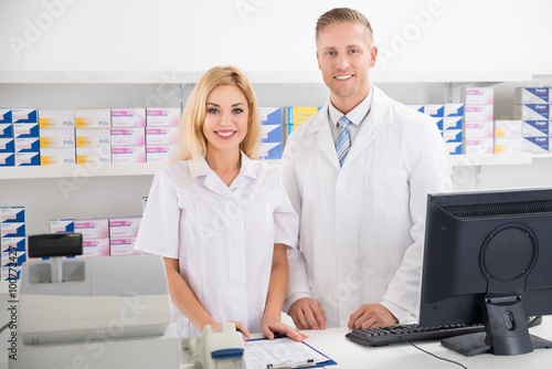 Pharmacists Smiling At Counter In Pharmacy Plakat