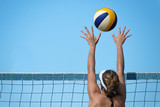 Beach volleyball player jumps on the net and tries to blocks the ball