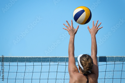 fototapeta na ścianę Beach volleyball player jumps on the net and tries to blocks the ball