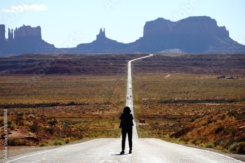 Poster Tourist photographing the famous view from road US 163 in Monument Valley Park,
