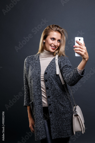 Sexy Beauty Girl with natural Make up. Fashion Blonde Portrait of a girl dressed in fur coat posing on a grey background.